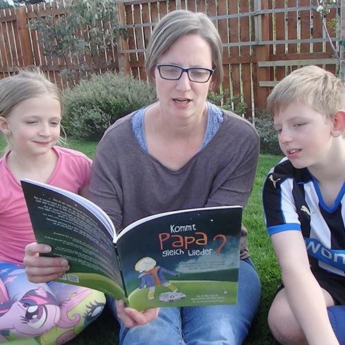 """Elke liest Alex und Olivia aus """"Kommt Papa gleich wieder?"""" vor."""