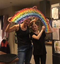 Olivia and Elke holding up their paper mache rainbow